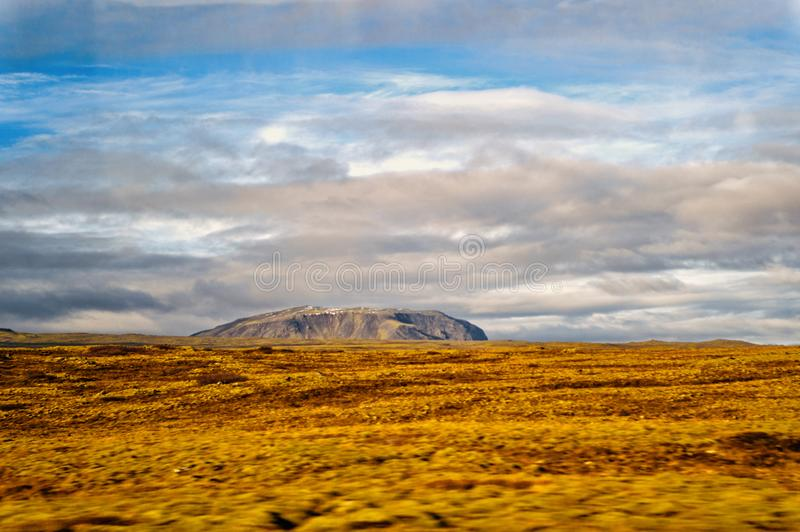 Landscape view with grass field in reykjavik, iceland. autumn landscape on cloudy sky. weather and climate. nature and. Ecology. high mountain in reykjavik royalty free stock photography