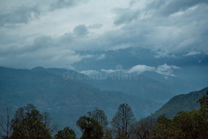 Landscape view of green hills covered with forest under floating clouds during late evening time. In Nepal royalty free stock photography