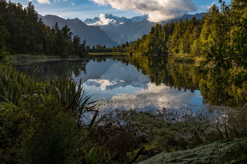 A landscape view of the incredibly beautiful Lake Matheson, New Zealand with the reflection of the stunning Southern Alps royalty free stock photo