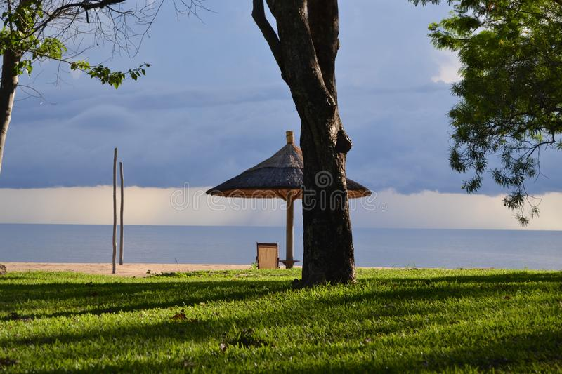 Landscape view of Lake Malawi tourist destination. Landscape view of Lake Malawi as a tourist destination. Beautiful grass field, and the lake and a storm and stock photography