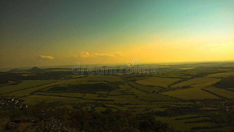 Landscape. View from the mountain Bořeň in Czech Republic. Nice green fields and beautiful sky without clouds. Industry in backround royalty free stock images