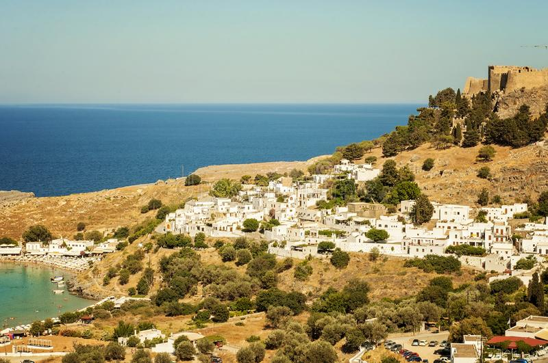 A landscape view from the mountain to a little village Lindos in Rhodes, Greece and an old castle on the background. A landscape view from the mountain to a stock images