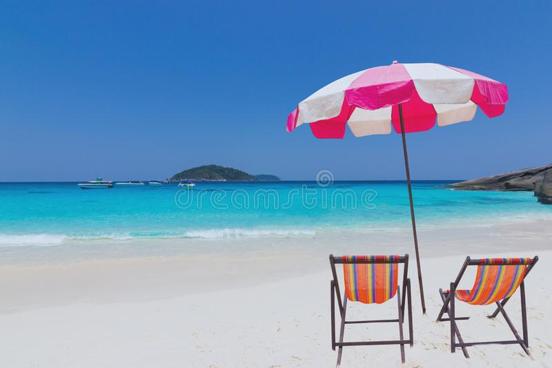 Landscape view ocean beautiful blue sky and boat with  Pink umbrellas with Empty chairs on a sandy. Sea beach, Similan Island Thailand copy space for text royalty free stock photography