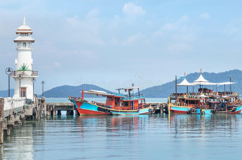 Landscape view of public white lighthouse on pier of Bang Bao fishing village with fishing boats mooring at Koh Chang Island,Trat,. Thailand in sunny day stock photography