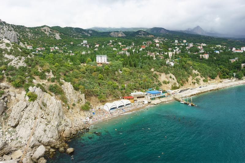 Landscape view from the rock Diva on the resort village Simeiz. Over the tops of the mountains hanging rain clouds, and the beach. Is Sunny. Changeable weather stock images