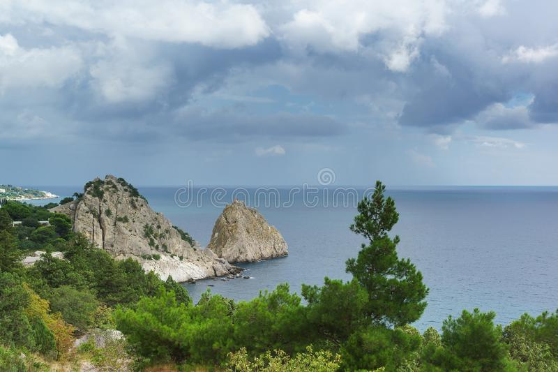 Landscape view of the rocks of Panea and Diva, protruding into the calm Black sea. Pine and juniper trees grow on the shore in. Simeiz village. Crimea, Yalta stock photo
