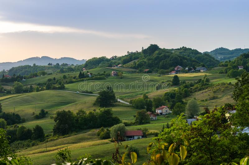 Landscape view of rolling hills during sunset in autumn, Zagorje region in Croatia, Europe. Landscape view of rolling hills with scattered houses, trees, roads royalty free stock photography