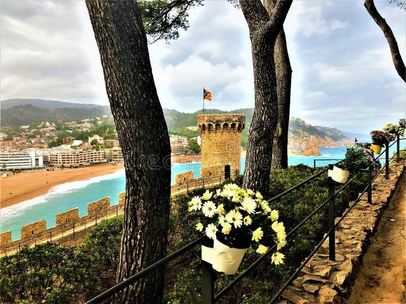 Landscape, sea, trees, flowers and medieval tower in Tossa de Mar, Spain. Landscape, view, sea, medieval tower, trees, light, flowers, fairytale, beauty royalty free stock images