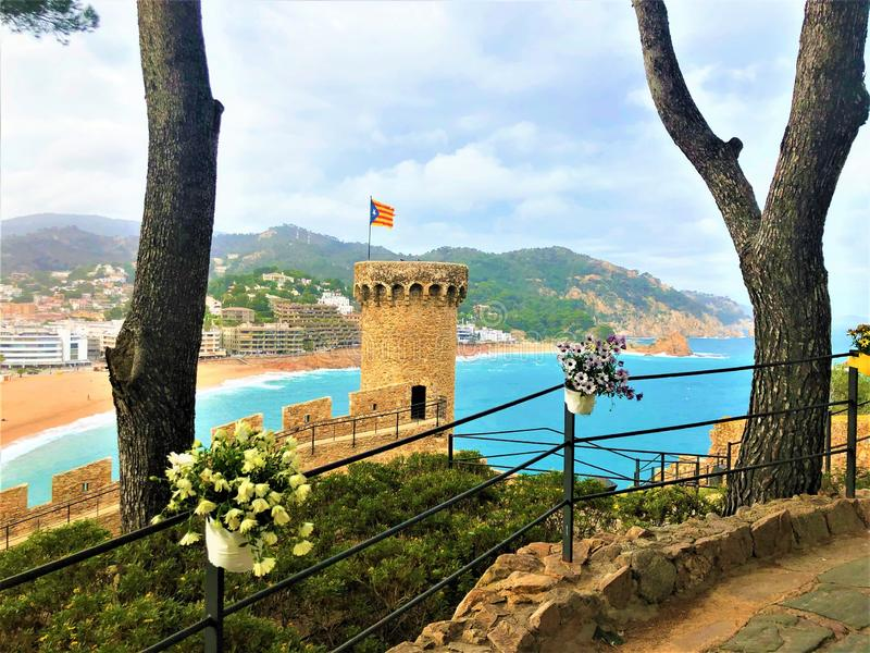 Landscape, sea, trees, flowers and medieval tower in Tossa de Mar, Spain. Landscape, view, sea, medieval tower, trees, light, flowers, fairytale, beauty royalty free stock photography