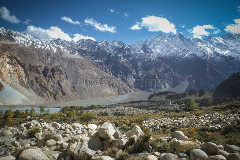 Landscape view of snow capped mountains and meadow in Passu. stock photo