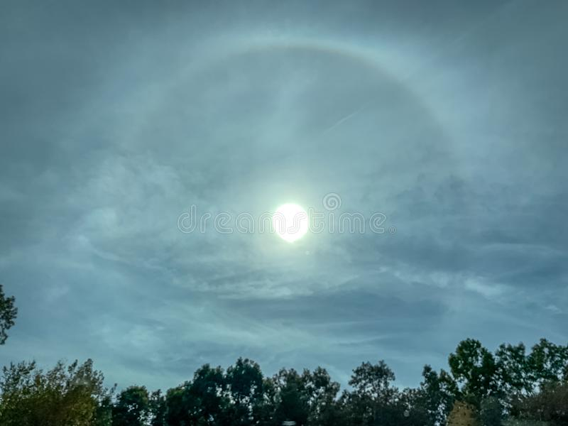 Landscape view of stunning sun halo over tree-lined landscape. royalty free stock images