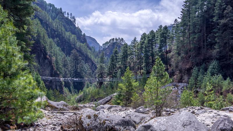 Landscape view of suspension bridge over the river. Landscape view of suspension bridge over the river, surrounded by green forest. Sagarmatha Everest National stock photography