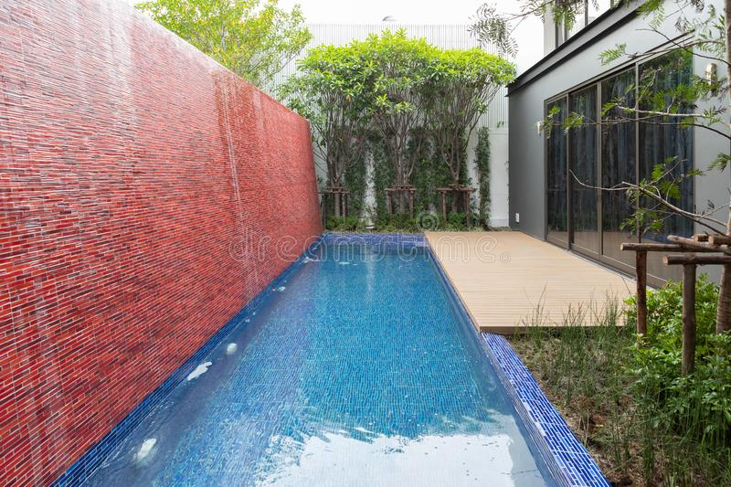 Landscape view of swimming pool with brick wall waterfall at exterior backyard luxury house stock images