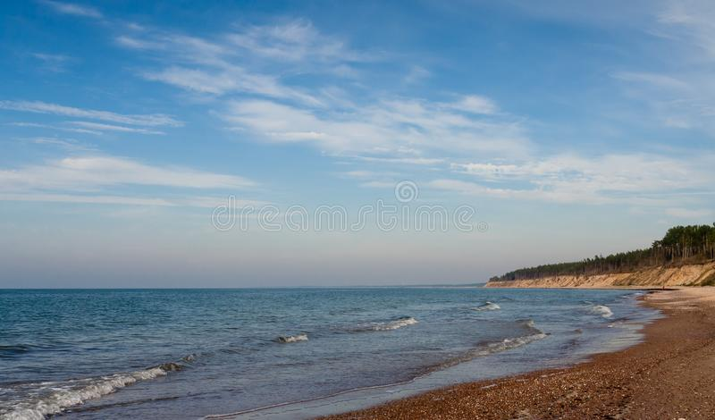 Landscape with views of the Baltic Sea. On the banks of large and small stones and sand, wet stripe up water, small waves and endless horizon, blue sky and royalty free stock photos