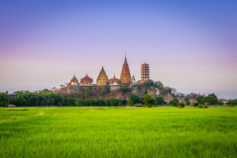 Landscape of Wat Tham Sua Temple Tiger Cave Temple in Sunset scence with Jasmine rice fields at Kanchanaburi Province. Thailand. Is an important landmark that stock image