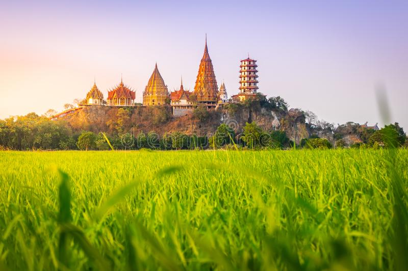 Landscape of Wat Tham Sua Temple Tiger Cave Temple in Sunset scence with Jasmine rice fields at Kanchanaburi Province. Thailand. Is an important landmark that royalty free stock images