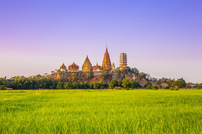 Landscape of Wat Tham Sua Temple Tiger Cave Temple in Sunset scence with Jasmine rice fields at Kanchanaburi Province. Thailand. Is an important landmark that royalty free stock photography