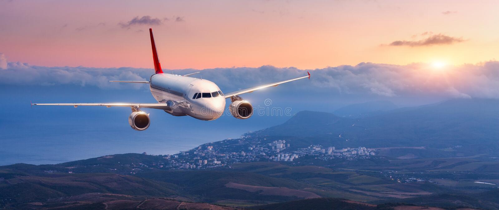 Landscape with white airplane is flying in the orange sky. Passenger airplane. Landscape with white airplane is flying in the orange sky with clouds over royalty free stock photo