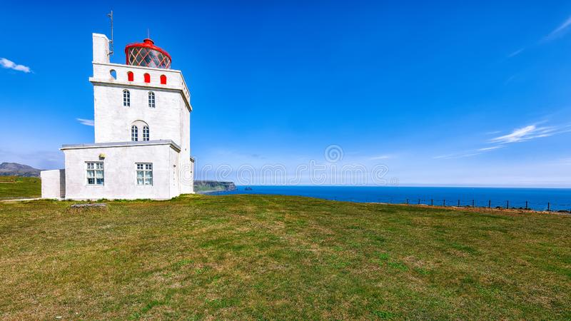 Landscape with white lighthouse at Cape Dyrholaey royalty free stock photography