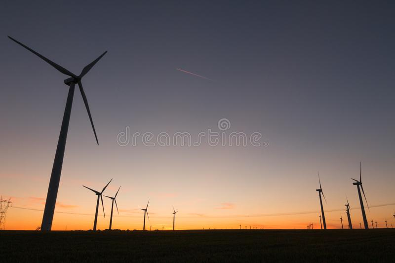 A landscape with windmills in a wind farm at sunset generating alternative and green energy source.  stock photo