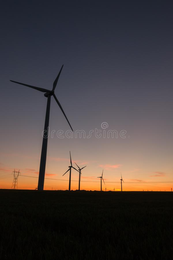 A landscape with windmills in a wind farm at sunset generating alternative and green energy source.  royalty free stock photos