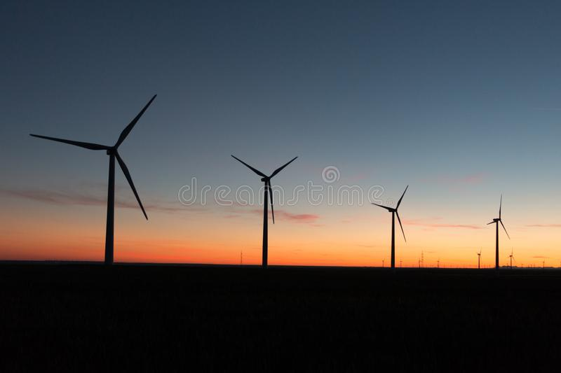 A landscape with windmills in a wind farm at sunset generating alternative and green energy source.  stock photography
