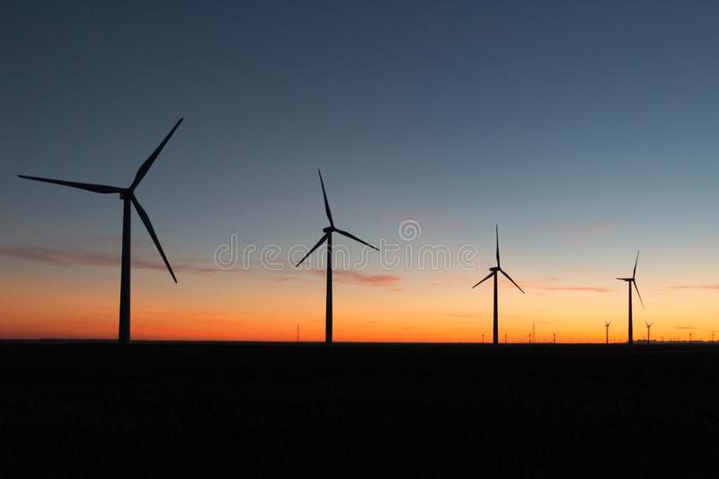 A landscape with windmills in a wind farm at sunset generating alternative and green energy source.  stock photos