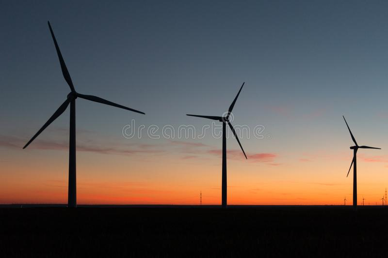 A landscape with windmills in a wind farm at sunset generating alternative and green energy source.  royalty free stock images