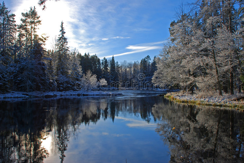 Landscape after winter frost. Landscape of trees and placid river after winter frost; reflection of sky and trees on surface of water royalty free stock photos