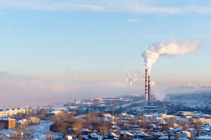 Landscape of a winter industrial zone with smoking chimneys. Of thermal power station and frosty haze stock image