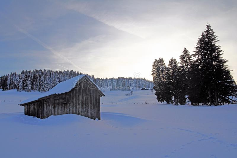 A landscape in winter with a wooden hut and trees royalty free stock photos