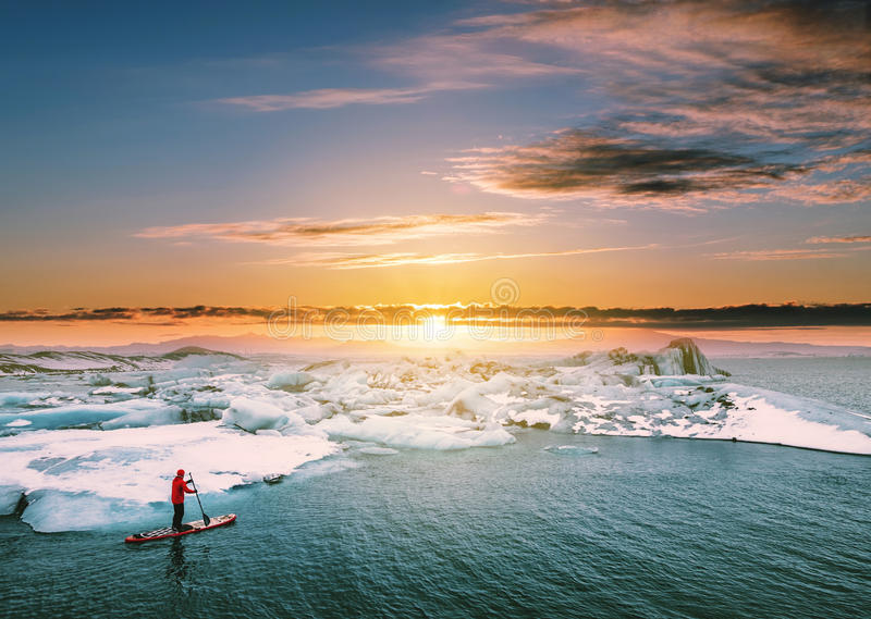 Landscaped, Beautiful glacier lagoon in sunset with a guy paddle boarding royalty free stock photo