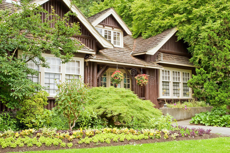 Landscaped log cottage in woods. A view of a small log cottage in the woods with colorful flower landscaping royalty free stock image