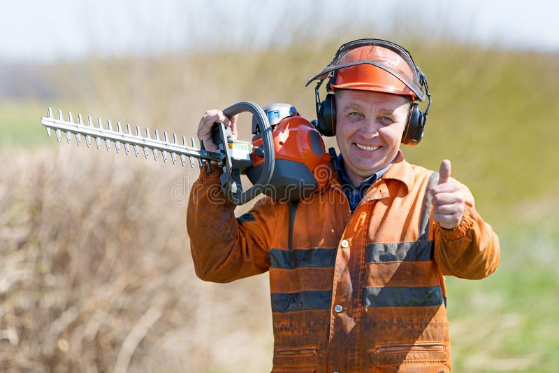 Landscaper feliz Man Worker no uniforme com sinal gersturing da aprovação da ferramenta do ajustador de conversão fotografia de stock royalty free