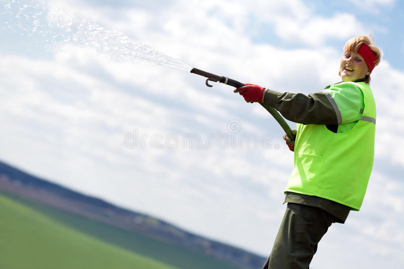 Landscaper gardener watering lawn stock photos