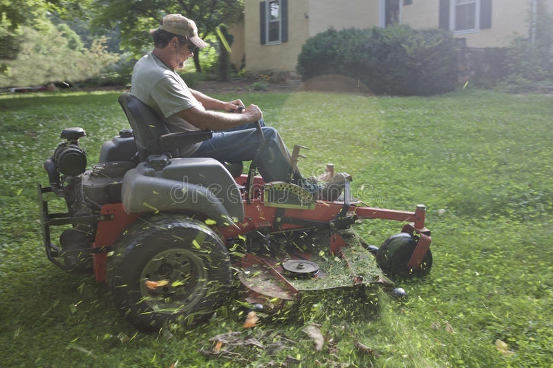 Landscaper on riding lawn mower royalty free stock photos