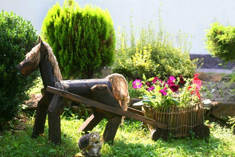 landscaping Decoratief houten paard met een kar Bloembed met bloemen stock afbeelding