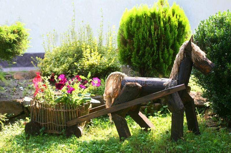 Landscaping. Decorative wooden horse with a cart. Flowerbed with flowers. royalty free stock image