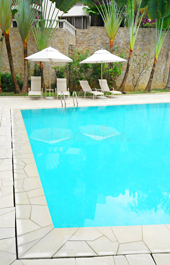 Landscaping at modern resort pool. Condominium outdoor recreational premise - An image of the clear blue pool of a private condominium residence. With sunshade royalty free stock photography