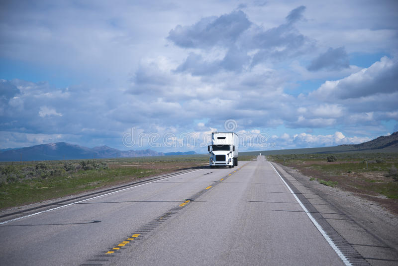 Landscaping with white semi-truck and long road in Nevada. Popular model of white semi truck with a comfortable interior cabin for the professional long haul stock photos