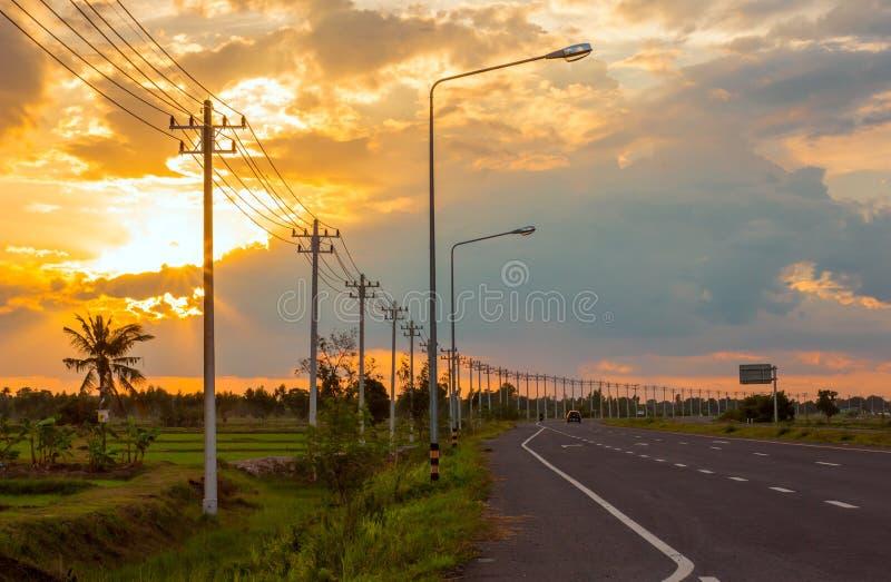 Landschaft auf den Gebieten und der Hintergrund, orange Himmel, Dämmerung und elektrische Pfosten auf der Straße stockbild