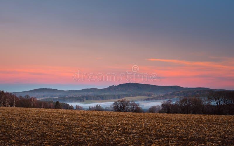 Landschaft bei Sonnenuntergang, im Vordergrund und bei Bäumen, im Tal weißer Nebel, im Hintergrund Wald und Berge lizenzfreie stockbilder
