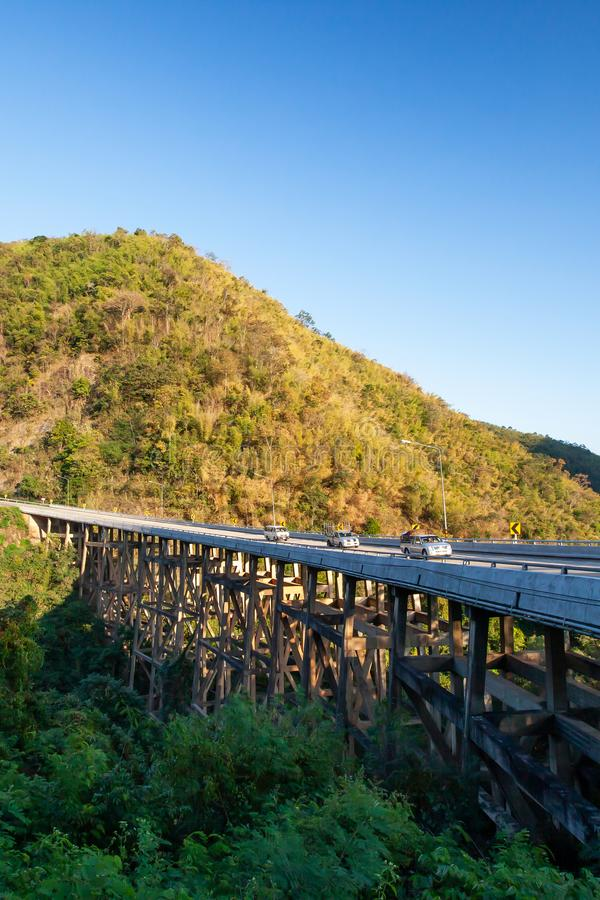 Landschaft der Bärngebirgsbrücke an der Dämmerung, am goldenen Sonnenuntergangglanz auf dem Autofahren über die Brücke und am Geb stockfotografie