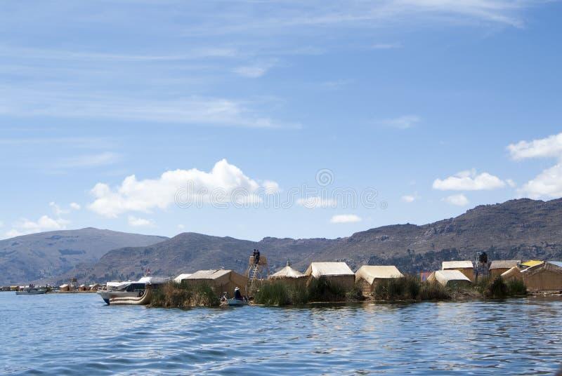 Landschaft der sich hin- und herbewegenden Inseln Uros in den magischen blauen Farben des Titicaca Sees mit dem Anden-Gebirgszug  lizenzfreies stockbild
