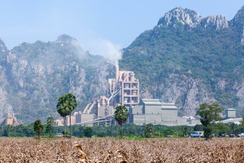 Landschaft der Zementfabrik in Thailand, Maisfeldvordergrund, Kalksteingebirgszughintergründe stockfoto