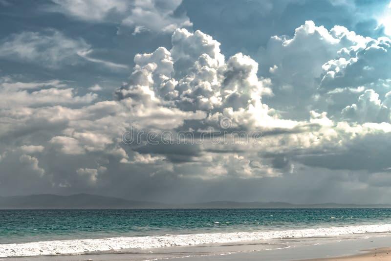Landschaft des merkwürdigen Wetter-Phänomens wegen des Klimawandels, drastische dunkle Wolken neben natürlichem Strand enthalten  lizenzfreie stockbilder