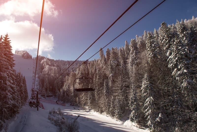 Landschaft des Skiaufzugs in den Bergen am schneebedeckten Tag bei Sonnenuntergang stockfotografie