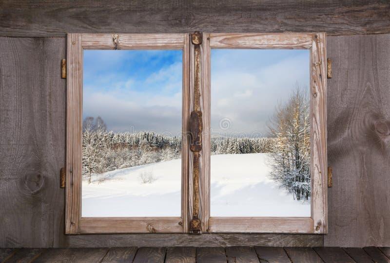 Landschaft des verschneiten Winters Ansicht aus einem alten rustikalen hölzernen Fenster heraus stockfotografie