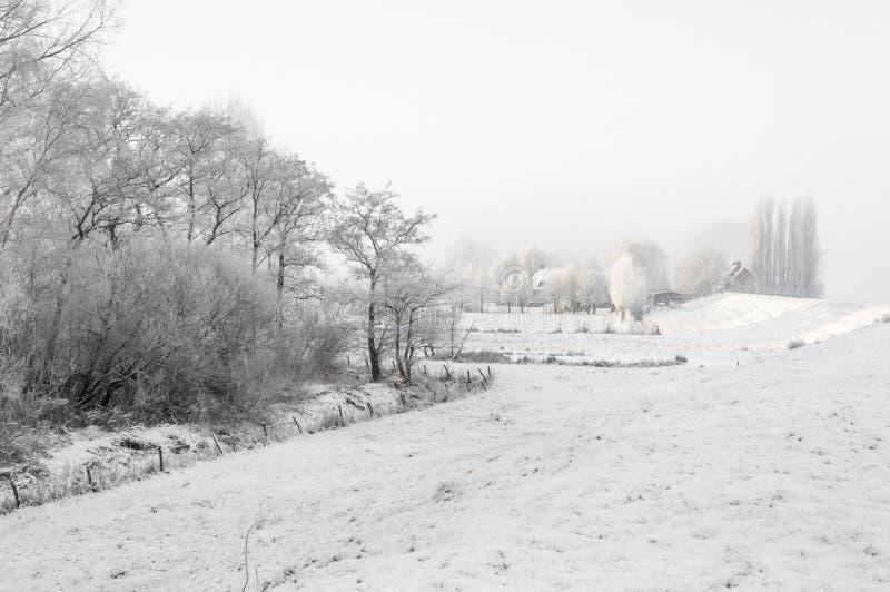 Landschaft des verschneiten Winters mit Häusern nahe bei einem Graben. lizenzfreie stockfotos