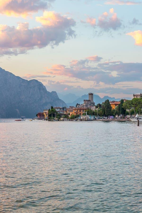 Landschaft in Italien: Sonnenuntergang bei Lago di Garda, Malcesine: See, Wolken und Dorf stockfotos